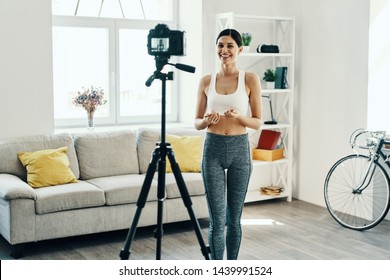 Sharing experience. Beautiful young woman in sports clothing making social media video while spending time at home