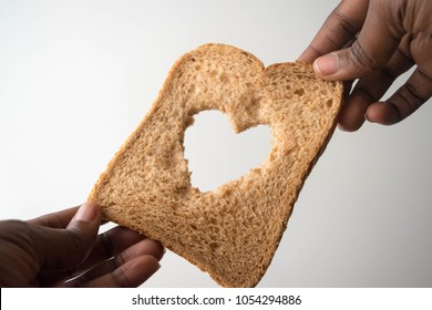 Sharing food with love - African American child hand with a slice of bread, isolated