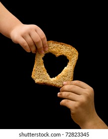 Sharing food with the needy - kids hands with a slice of bread