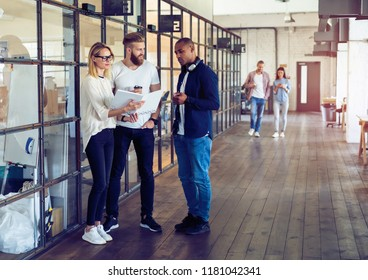 Sharing fresh ideas. Group of young business people in smart casual wear talking and smiling while standing in the office hallway