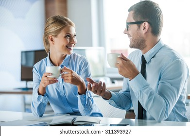Sharing fresh news. Two joyful young people in formalwear holding cups of coffee and discussing something while working together
