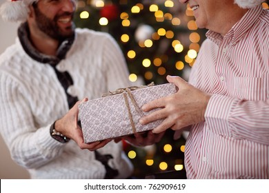 sharing gift on Christmas-Father giving present to son close up