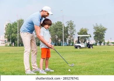Sharing with golf experience. Cheerful young man teaching his son to play golf while standing on the golf course