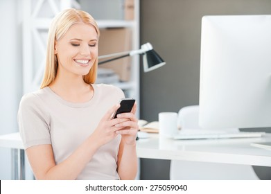 Sharing good news from colleagues. Beautiful young woman holding mobile phone and smiling while sitting near her working place in office
