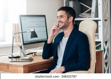 Sharing good news. Side view of handsome young man talking on the mobile phone and smiling while sitting at his working place in office