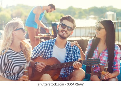 Sharing good time. Three cheerful young people bonding to each other and sitting on the bean bag with guitar while man barbecuing in the background