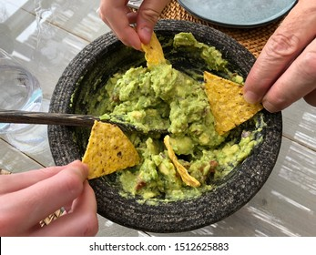 Sharing a guacamole dip with tortilla chips