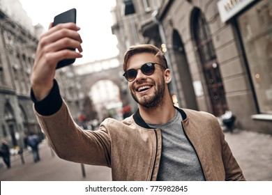Sharing happy selfie. Handsome young smiling man in casual wear taking selfie using his smart phone while standing outdoors