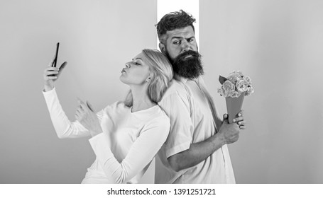 Sharing happy selfie. Woman capturing happy moment boyfriend bring bouquet flowers. Couple in love bouquet dating celebrate anniversary relations. Capturing moment to memorize. Taking selfie photo.