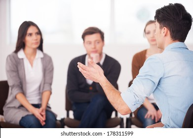 Sharing his problems with people. view of man telling something and gesturing while group of people sitting in front of him and listening