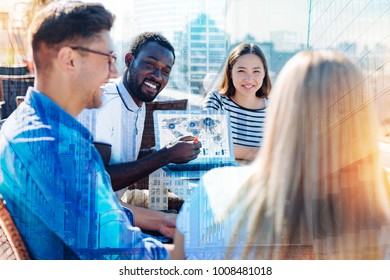 Sharing information. Attractive alert afro-american man smiling and showing his part of work on the laptop to his exuberant colleagues and they discussing it