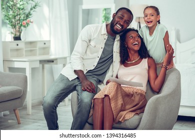 Sharing a laugh with family. Pleasing joyful contended glowing Afro-American cheerful family of three sharing a laugh and discussing a drawing made by a daughter while sitting on the chair
