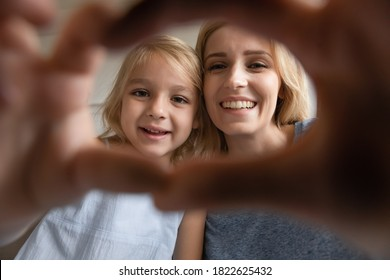 Sharing love. Affectionate happy young adult mother and daughter preschooler making selfie inside a heart shape of fingers, loving elder and younger sisters posing for self portrait looking at camera