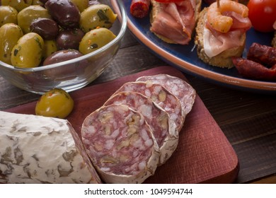 Sharing mixed spanish tapas starters on table. Olives, sandwiches, salami with walnuts and avocado