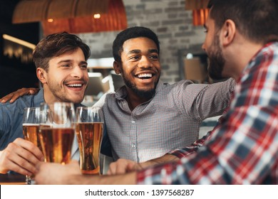 Sharing News. Diverse Friends Drinking Beer And Chatting In Bar