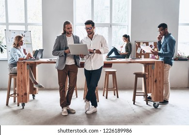 Sharing opinions. Full length of young modern people in smart casual wear smiling and discussing something while working in the creative office