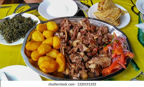 Sharing platter of a traditional Kenyan dish, Nyama Choma accompanied by kachumbari salad, sukuma wiki, chapati and roast potatoes. The roasted goat has been slow cooked outdoors. Eldoret, Africa.