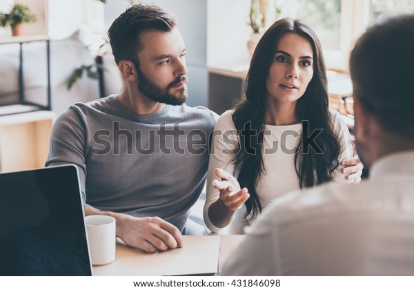 Sharing problems with psychologist. Confident young couple telling their problems to psychologist while sitting together at the desk