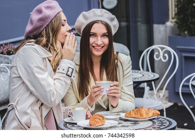 Sharing secrets with best friend. High-angle view of beautiful woman in beret whispering to her friend while drinking coffee in french cafe. Women friends gossiping during coffee time. French fashion.