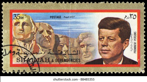 SHARJAH - CIRCA 1973: A stamp printed in Sharjan shows 35th president of USA John Fitzgerald Kennedy against statue of Mount Rushmore National Memorial, circa 1973.