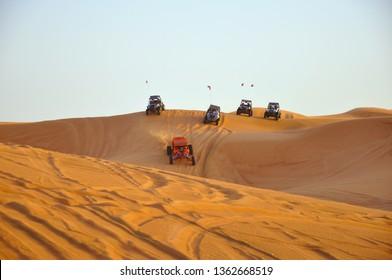 Sharjah desert Dubai, United Arab Emirates - 20.2.2012:  Tourists driving dune buggy in desert near Dubai, UAE