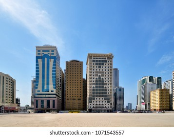 Sharjah, UAE - April 8. 2018. Multi-storey residential and office buildings with sand in foreground