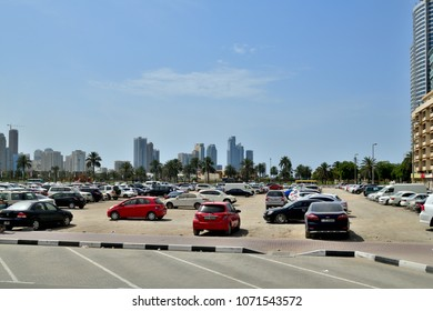 Sharjah, UAE - April 8. 2018. Parking in sand next to residential and office buildings