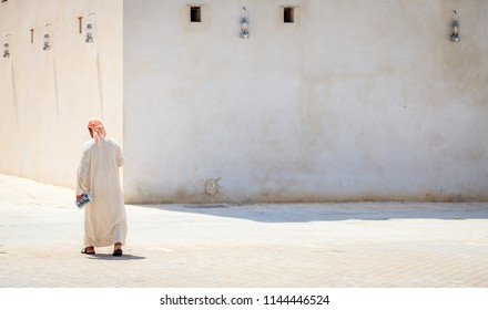 Sharjah, UAE, March 26, 2016: A local man in a traditional arab dress on a street in Sharjah, UAE