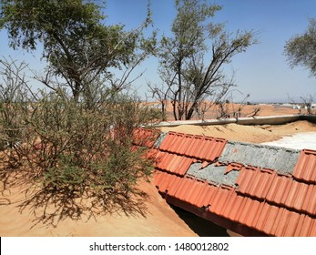 Sharjah, UAE - May 03, 2019: The Arabian desert sand slowly buries entire concrete houses in an abandoned village in Al Madam, Sharjah, UAE. The place is reputedly haunted by ghosts / spirits.