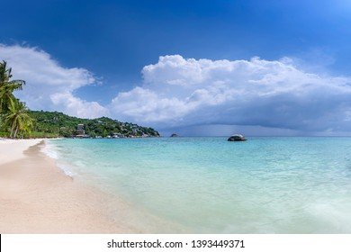 Shark Bay Koh Tao Thailand on the beach with blue skies with shark island in the background wide panorama coconut trees and clouds and clear water scuba paradise no people with copy space
