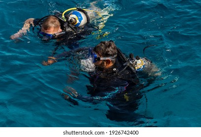 Sharm Ash Sheikh, Egypt - 01.18.2021. The scuba diving instructor helps the student. Tourists go diving during a cruise on the bay. Sea excursions to the reefs of the Red Sea.