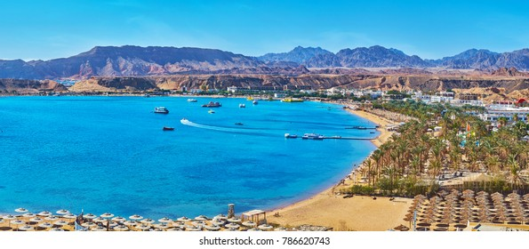 Sharm El Maya is one of the central districts of resort, that boasts scenic rocky landscape and beautiful beaches with palms and multiple sunshades, Sharm El Sheikh, Egypt.