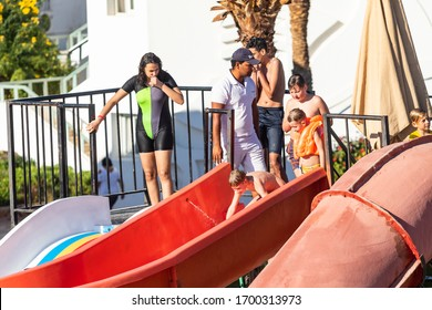 Sharm El Sheikh, Egypt - January 28, 2020: Adults and children swim in the pool, ride on the slides on a Sunny day. In other words, the concept of travel, vacation.