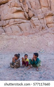 SHARM EL SHEIKH, EGYPT - JULY 9, 2009. Three children are sitting in the desert, and looking into the distance.