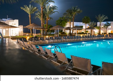 Sharm El Sheikh, Egypt - March 07, 2020: Beautiful view of the luxurious hotel pool in the moonlight. Rest area at an expensive resort. Swimming pool at night in one of the hotels near beach