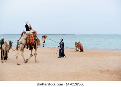 SHARM EL SHEIKH, EGYPT -  NOVEMBER 29: Tourist rides camel on beach with help of Egyptian man on November 29, 2013 in Sharm el Sheikh, Egypt. Up to 12 million tourists have visited Egypt in year 2013.