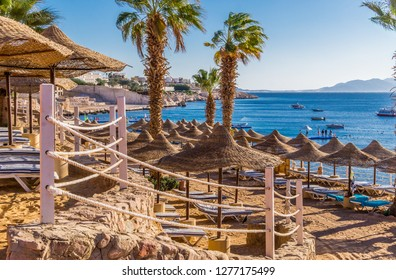 Sharm El Sheikh, Sinai / Egypt - December 18 2018: Beautiful sunny beach and parasols on the coast of the Red Sea in the city of Sharm El Sheikh, Egypt. Tourist recreation area on the Sinai Peninsula