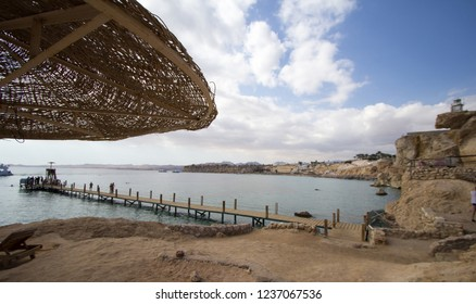 Sharm El-Shaikh, Egypt - November 2, 2018:- photo for  Red Sea coast  In the Egyptian city of Sharm el-Sheikh, which showing water and some rocks and beds and Tourists and  some of umbrellas. .
