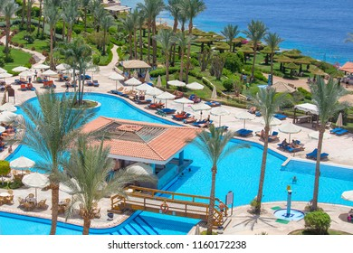 SHARM EL-SHEIKH, EGYPT - MAY 17, 2018: People swim and sunbathe in the swimming pool next to the red sea in the resort hotel in Sharm El Sheikh, South Sinai, Egypt