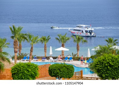 SHARM EL-SHEIKH, EGYPT - MAY 25, 2018: People rest in the swimming pool next to the red sea in the resort hotel in Sharm El Sheikh, South Sinai, Egypt