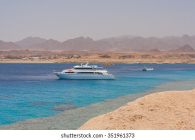 Sharm-El-Sheykh, Egypt - June 03, 2010 :: Egyptian beach with mountains and boat at Red sea