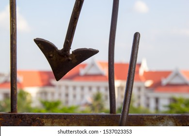 Sharp arrow of Fence protection along the wall against blue sky