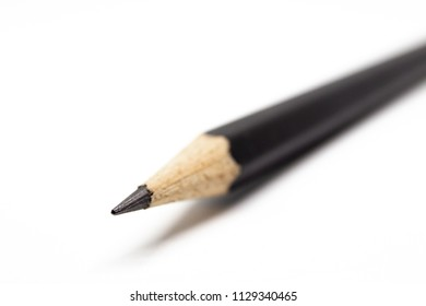 Sharp black pencil head in macro shot close up on white background.  Droped copy space on left side.