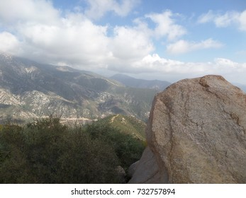 Sharp boulder on a hill side with distant clouds, California