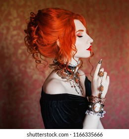 Sharp claws. Dark halloween attire. Goth woman is vampire with pale skin and red hair in black dress and necklace on neck. Girl witch with vampire claws. Gothic look. Goth outfit for halloween.