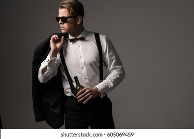 Sharp dressed man in black suit with bottle of wine.