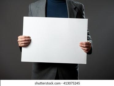 Sharp dressed man holding white blank billboard