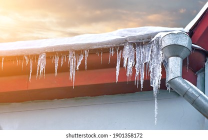 Sharp icicles hanging down from roof of the old residential building against sunny background. Transparent icicles on facade of building, dangerous icicles melt on rooftop, risk of  injury