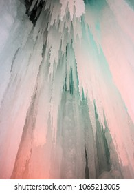 Sharp icicles illuminated in pink and blue hanging down from ice cave