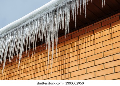 Sharp icicles and melted snow hanging from eaves of roof. Beautiful transparent icicles slowly gliding of a roof. Icicles on the eaves of the roof.